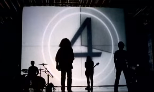 Van Halen in silhouette before a giant movie screen emblazoned with the number '4'