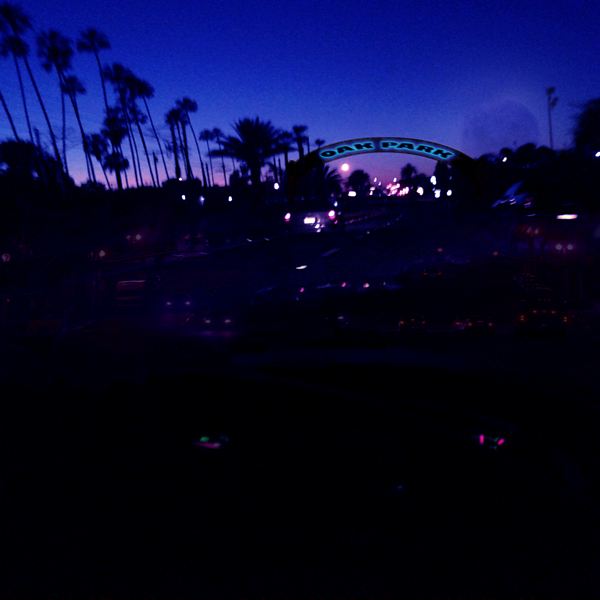 The neon Oak Park arch at night, the moon and palm trees loom on the horizon