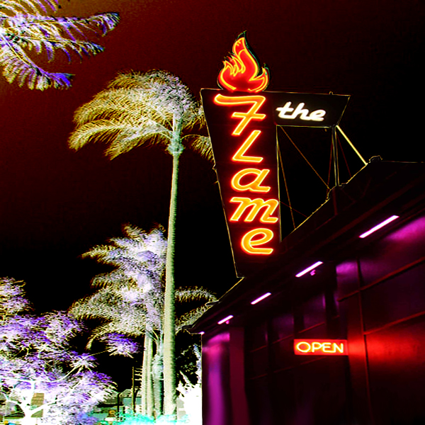 A negative image of the sign for The Flame nightclub (in Hillcrest), with palm trees swaying in the background