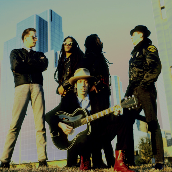 Mick Jones kneels with a guitar as B.A.D. stand behind him, skyscrapers looming in the background