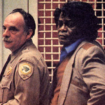 James Brown, serious in a suit, with the bailiff