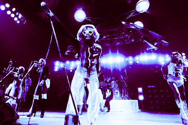 Funkadelic performing live on stage as the Mothership looms in the distance