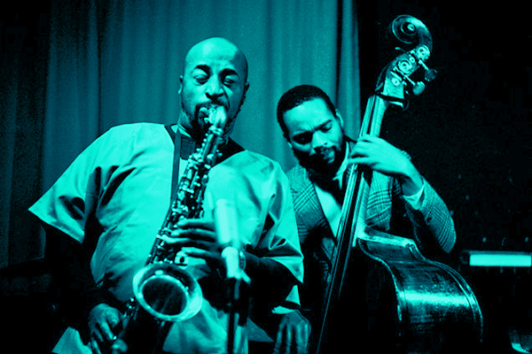 Yusef Lateef blows a saxophone as the bassist plays an upright in the background