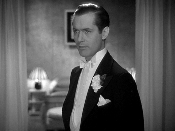 A besuited Robert Montgomery in the movie Faithless