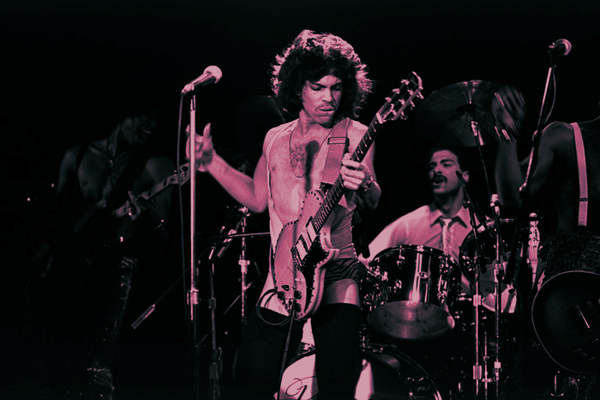 Prince lost in the guitar, live on stage, drummer and bassist in the background