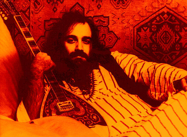 Démis Roussos decked out in trademark kaftan with a tapestry in the background