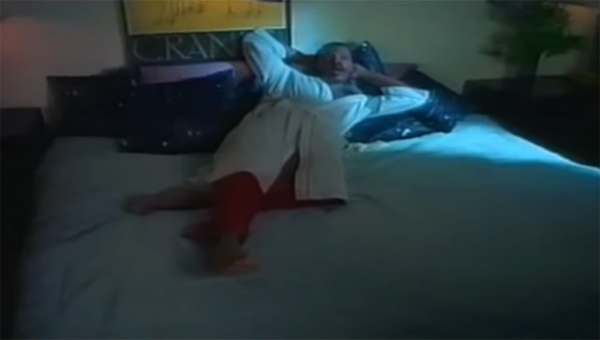 Alexander O'Neal reclines on a king size bed in his bathrobe