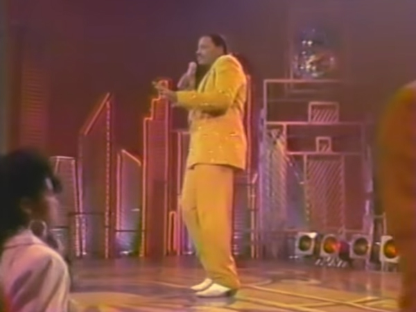 Alex sings on stage, dancing in a sparkling mustard suit