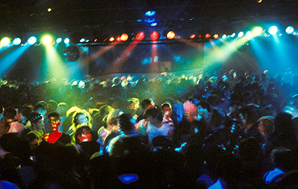 A massive crowd dances at an indoor rave