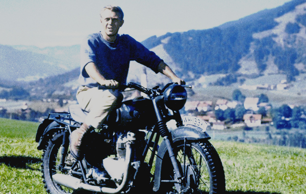 Steve McQueen rides a stolen motorcycle across the German countryside