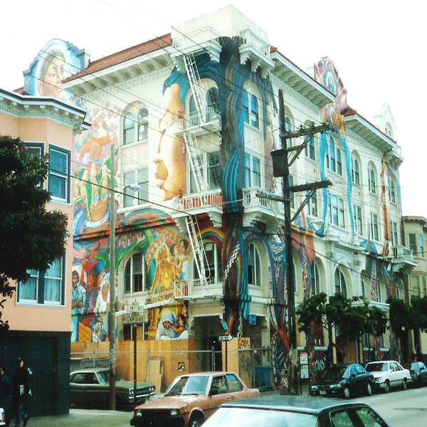 An apartment building in San Francisco's Mission District, adorned with a beautiful mural