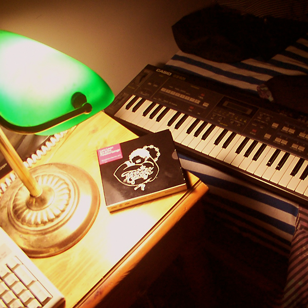 A desk with a keyboard, banker's lamp and a copy of Larry Levan Live At The Paradise Garage.  A Casio CZ-101 sits on the bed beside the desk.