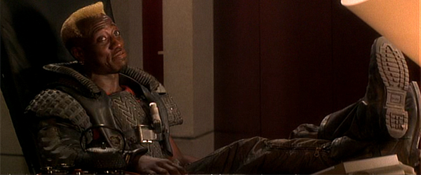 Simon Phoenix reclining in a chair after reprogramming the lights in Demolition Man.