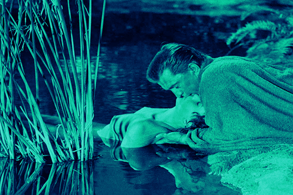 Jean Simmonds lays in a lake — her body hidden behind reeds — as Kirk Douglas kisses her from above