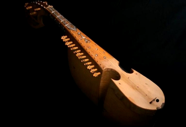 A wooden Rabaab (a stringed Persian instrument) leaning against a black backdrop