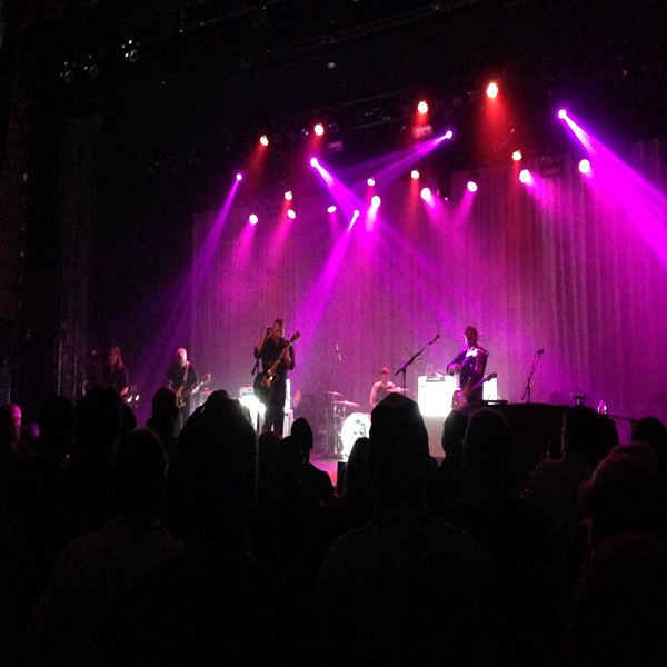 The Afghan Whigs playing live on stage (beneath magenta lights)