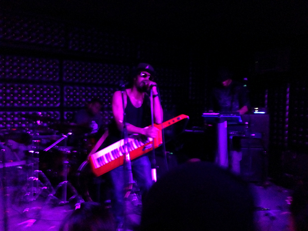 Dâm-Funk holds keyboard as he performs with band on stage beneath ultraviolet lights