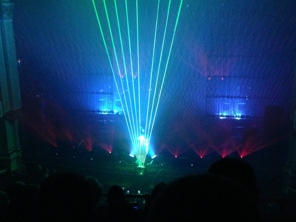 Nine green laser beams fan out from the floor while Jarre moves his hands across the beams