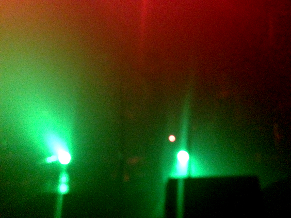 Two lights give off a greenish glow in the mist