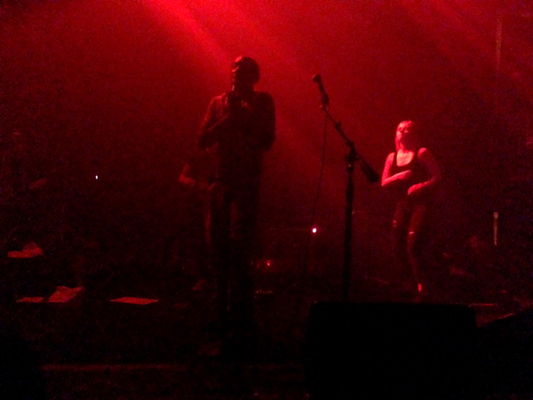 Tricky stands at center stage as Marta dances in the background
