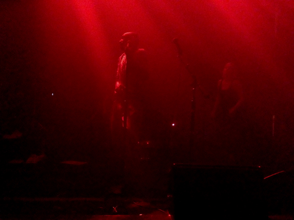 Tricky grasps the microphone, looking to the drummer, as Marta dances in the background (beneath the infrared glow)